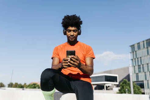 Young sportsman sitting on steps, using smartphone and listening to music - JRFF03725