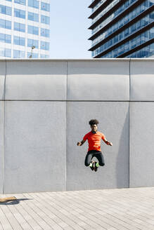 Young man doing jumps with a gray wall in the background - JRFF03737