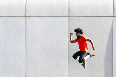 Young man doing jumps with a gray wall in the background - JRFF03740