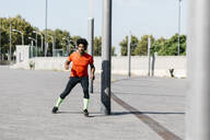 Young man jogging in the city, listening to music - JRFF03743