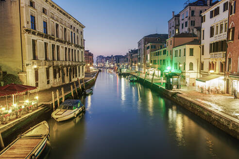 Evening canal view of low rise traditional buildings and wooden wharf pilings with moored boats, Venice, UNESCO World Heritage Site, Veneto, Italy, Europe - RHPLF10043