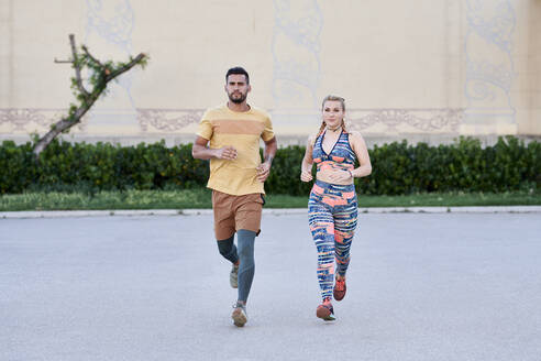 Man and woman running in the city - JNDF00086