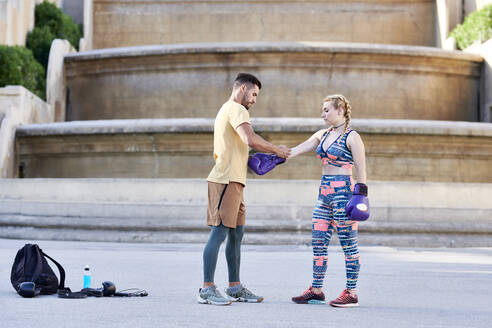 Fitness coach practicing boxing class with young woman outdoors in the city putting on boxing glove - JNDF00095