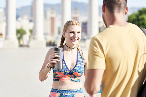 Happy woman with man finishing workout outdoors in the city - JNDF00101