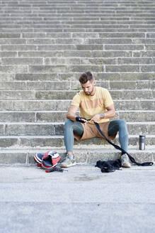Boxer sitting on stairs applying bandage - JNDF00104
