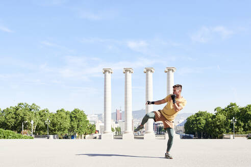 Man doing kickboxing exercise outdoors in the city - JNDF00107