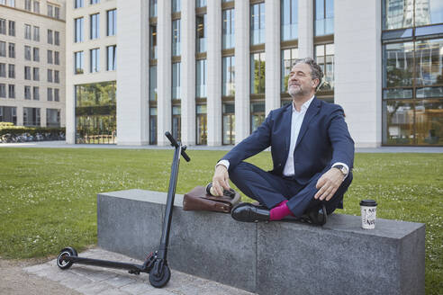 Relaxed mature businessman sitting on wall in the city - RORF01845