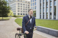 Mature businessman with bicycle in the city - RORF01848
