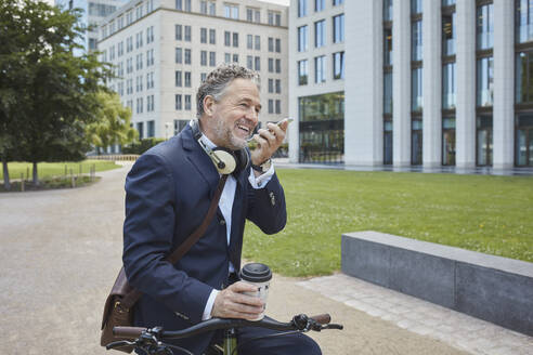 Mature businessman with bicycle using smartphone in the city - RORF01851