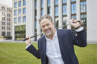 Portrait of happy mature businessman with golf club in the city - RORF01857