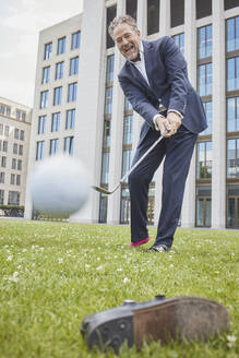 Happy mature businessman playing golf on lawn in the city - RORF01860