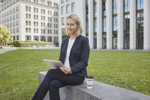 Businesswoman sitting on a wall in the city using tablet - RORF01872