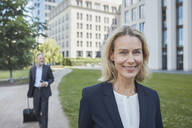Porrait of smiling blond businesswoman in the city with businessman in background - RORF01881