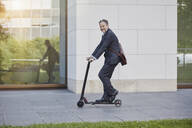 Businessman on e-scooter passing office building in the city - RORF01887