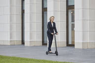 Businesswoman on e-scooter passing office building in the city - RORF01890