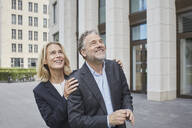 Happy businessman and businesswoman in the city looking up - RORF01905