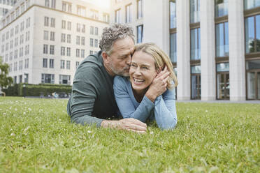 Happy mature couple lying on lawn in the city - RORF01923