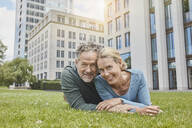 Portrait of happy mature couple lying on lawn in the city - RORF01926