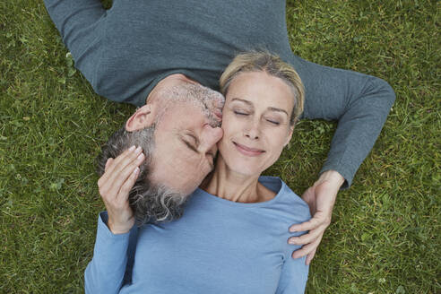 Top view of affectionate mature couple lying in grass - RORF01929
