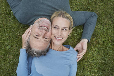 Top view of happy mature couple lying in grass - RORF01932