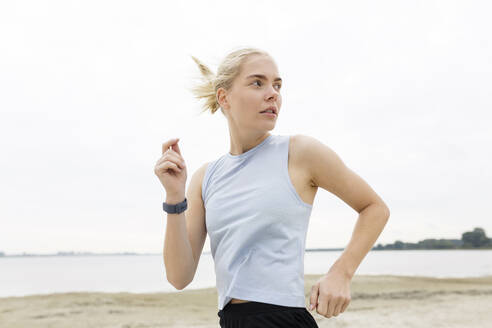 Young woman jogging with fitness tracker - JESF00308