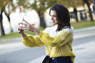 Brunette woman taking a selfie in the city - JSRF00563