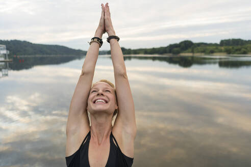 Happy young woman raising her arms at a lake - JOSF03591