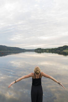 Young woman at a lake woth outstretched arms - JOSF03600