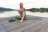 Young woman drinking coffee from cup at a lake - JOSF03603