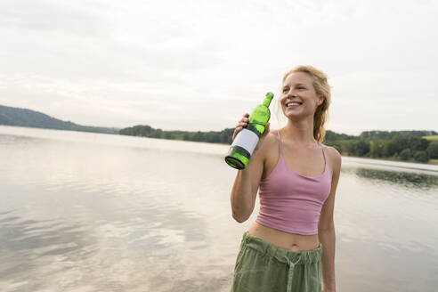 Happy young woman drinking water at a lake - JOSF03624