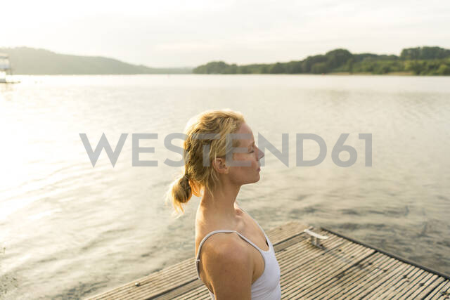 Young woman with closed eyes on a jetty at a lake - JOSF03630 - Joseffson/Westend61