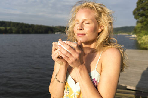 Young woman dwith closed eyes holding a cup at a lake - JOSF03639