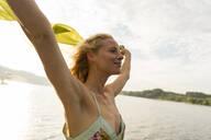 Young woman holding a cloth at a lake - JOSF03642