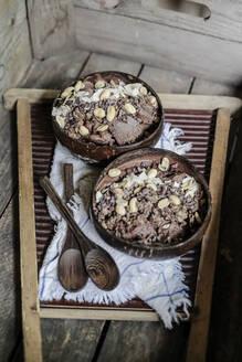 Nicecream Schokolade, Eiscreme aus Bananen mit Kakao und Erdnussbutter, Kokoschips, Erdnüsse, Kakaonips, Granola, Kokosschüssel und Löffel, Studio - STBF00384