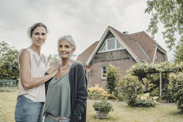 Mother and daughter standing in garden, inf ront of their house - JOSF03649 - Joseffson/Westend61