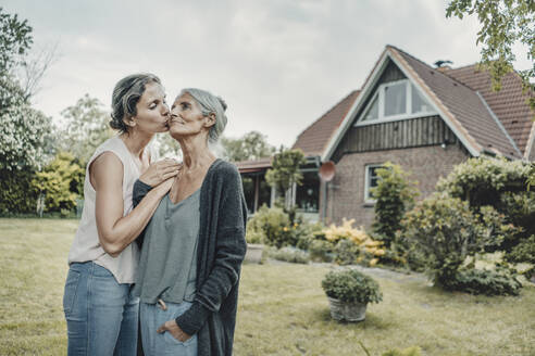 Daughter kissing mother in garden, in front of their house - JOSF03652