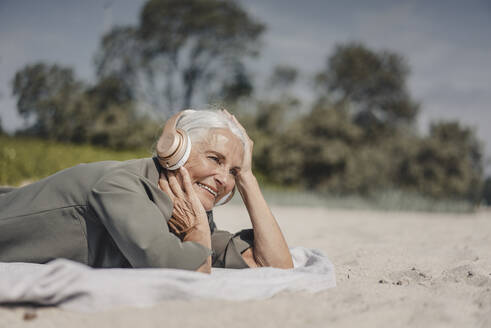 Senior woman listening music with headphones on the beach - JOSF03688