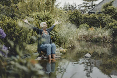 Senior woman sitting at garden pond, listening music - JOSF03721