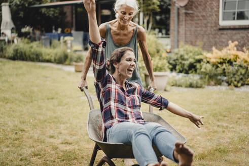 Mother pushing daughter, sitting in push cart, through the garden - JOSF03727