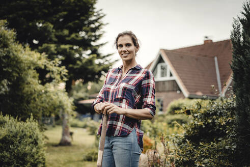 Proud home owner standing in her garden with a spade - JOSF03730
