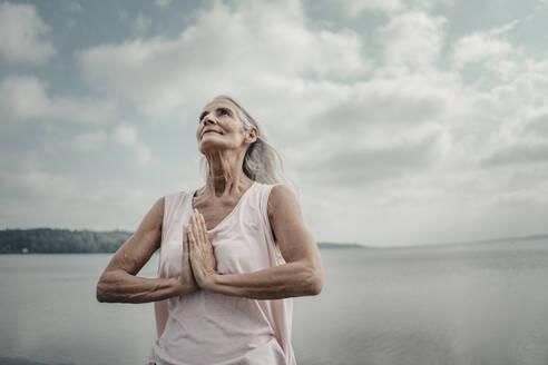 Senior woman meditation at the sea - JOSF03754