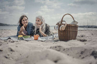 Mother and daughter having a picnic on the beach - JOSF03760