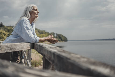 Senior woman standing on bridge, relaxing with eyes closed - JOSF03766