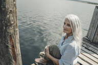 Senior woman sitting on jetty, relaxing at the sea - JOSF03772