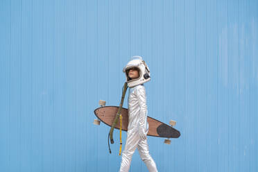 Kid dressed as an astronaut with longboard - DAMF00038