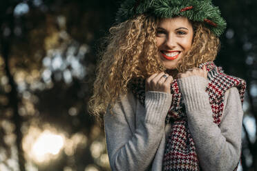 Portrait of young woman wearing Christmas wreath on her head - DAMF00056