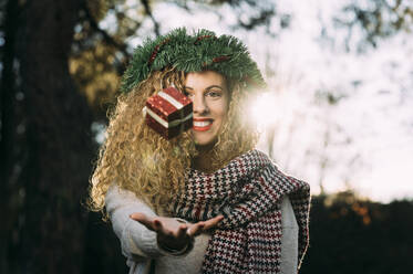 Portrait of smiling young woman with Christmas wreath on her head juggling with Christmas present - DAMF00059