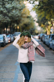 Portrait of happy young woman wearing Christmas wreath on her head dancing on the street - DAMF00062