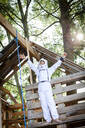 Young boy as a superhero, astronaut playing in a tree house - HMEF00541