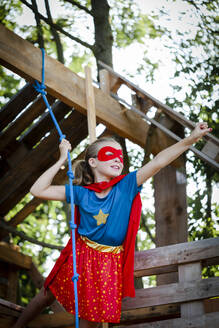 beautiful superhero girl playing in a beautiful, tree house in the afternoon sun, lower austria, austria - HMEF00565